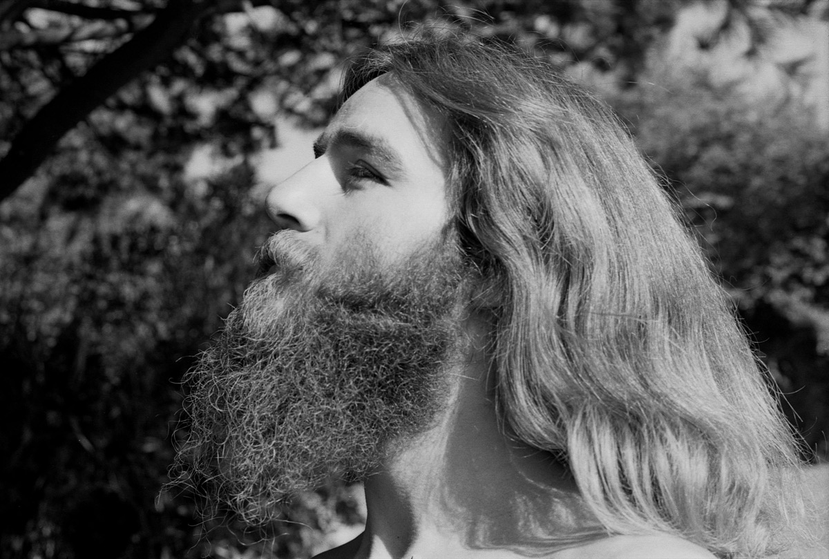Portrait of 1970s hippie man with beard and long hair being spiritual in Berkeley, California in the 1970s