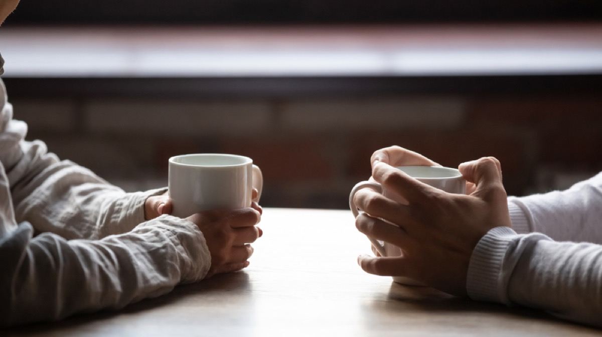 Closeup of couple's hands having coffee at table