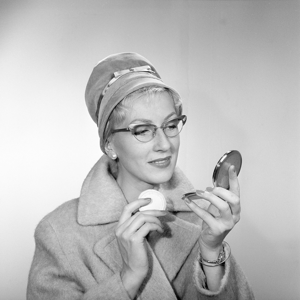 1950s makeup. A young woman is looking at herself in her pocket mirror and improves on her makeup. She is wearing a fashionable hat, typical 50s glasses and a coat. 1950s