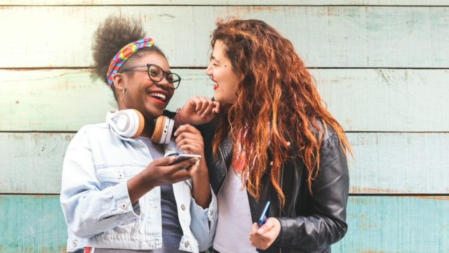 Two young women friends laughing