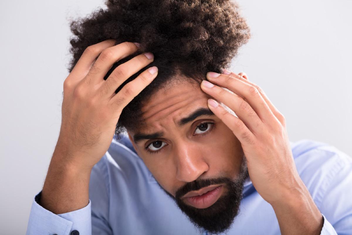 Young Black Man Examines Hair Loss