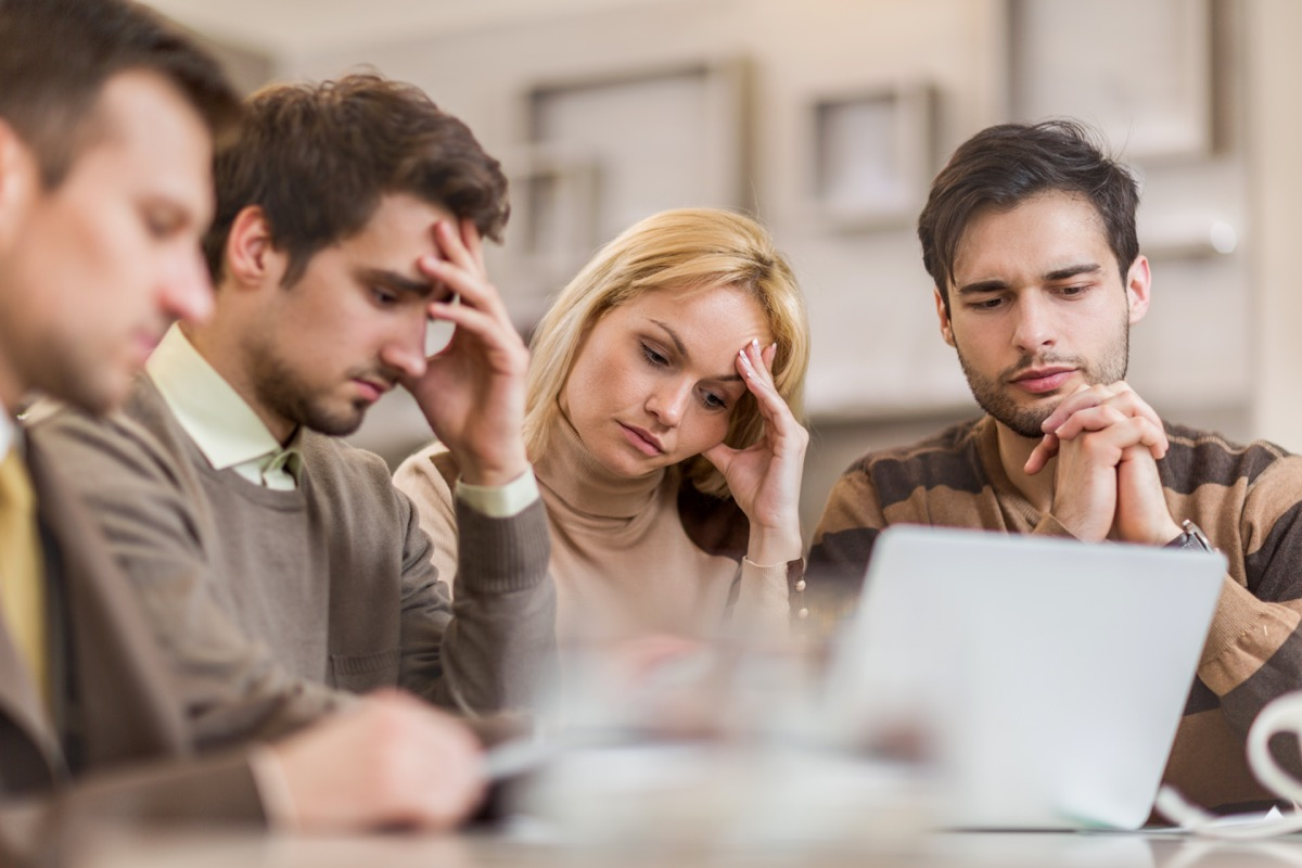 Small group of worried business people using wireless technology and working in the office.