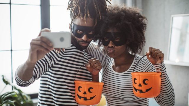 Young couple celebrating Halloween. They wear costumes, smiling, taking selfie and enjoy in holiday, diy halloween costume