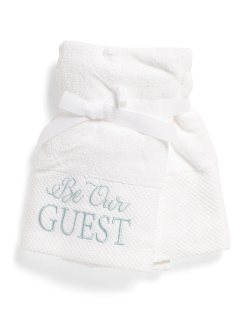 """white hand towel with """"be our guest"""" written on it, bathroom accessories"""
