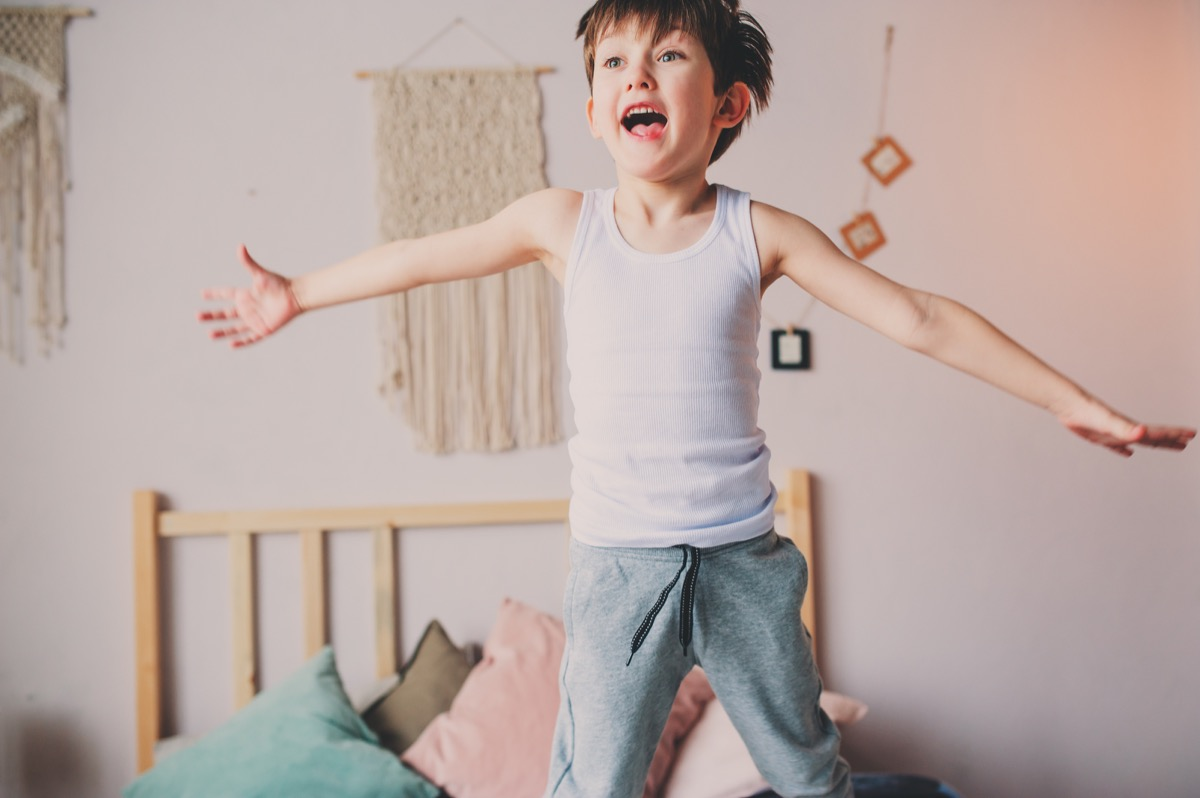 happy naughty boy jumping in bed in early morning. Hyperactive kids, casual lifestyles.
