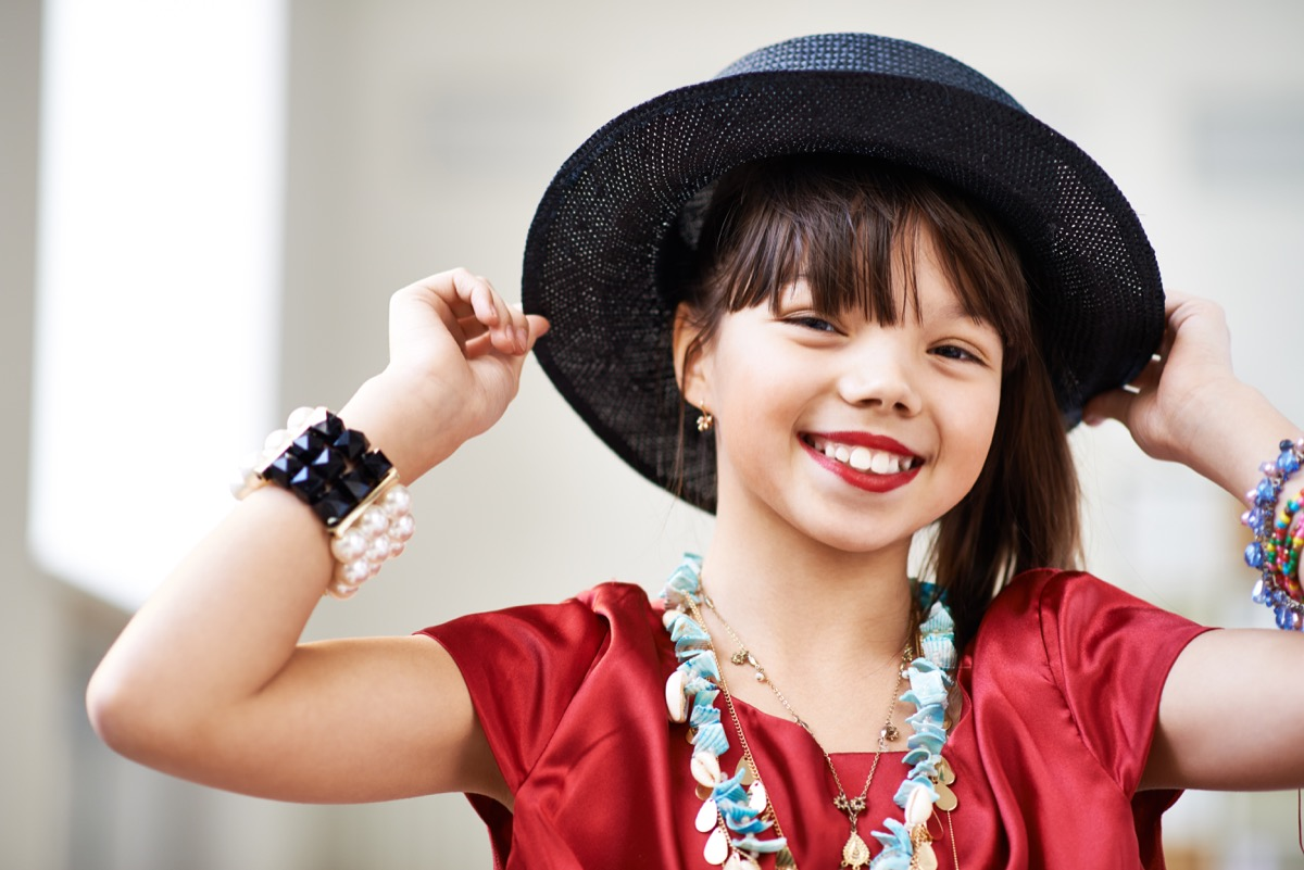 Charming girl with red lipstick wearing adult dress with hat and accessories looking at camera