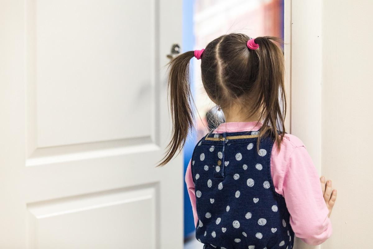Little girl peeking through a classroom door Classroom Surfaces Germs