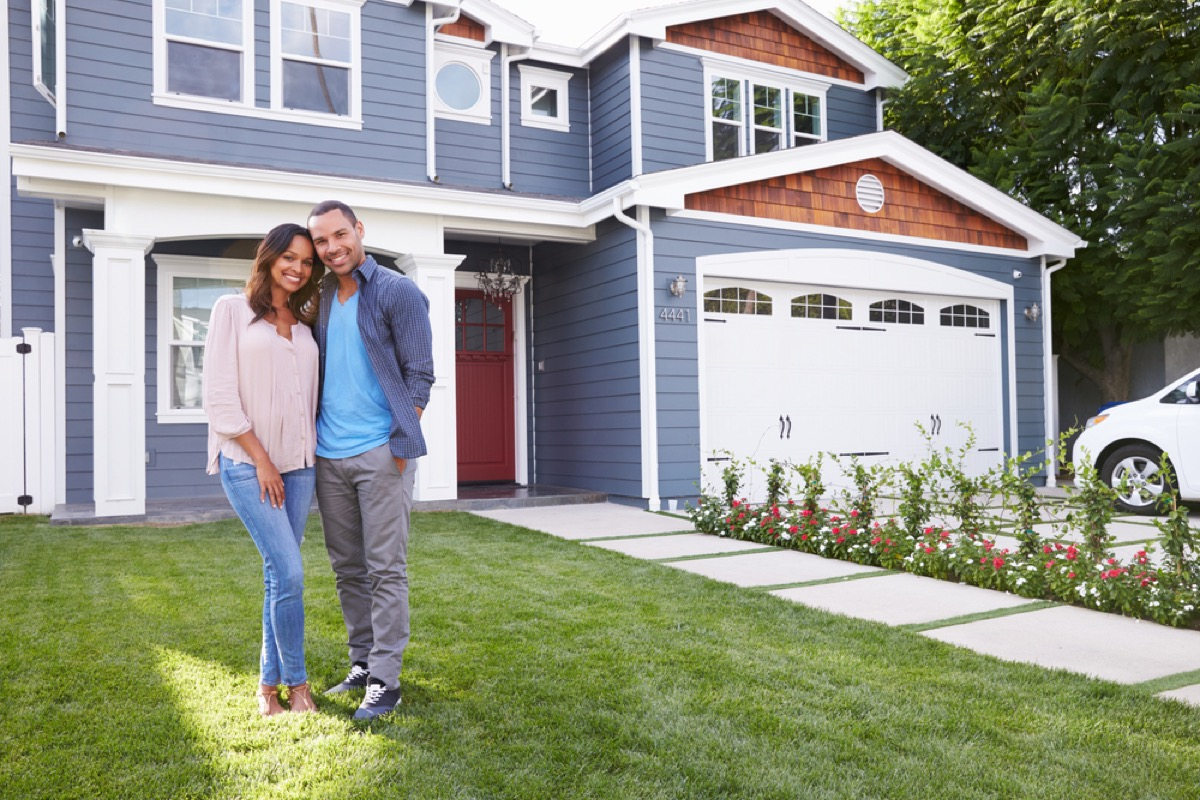 black couple standing in front of suburban house, fire prevention tips