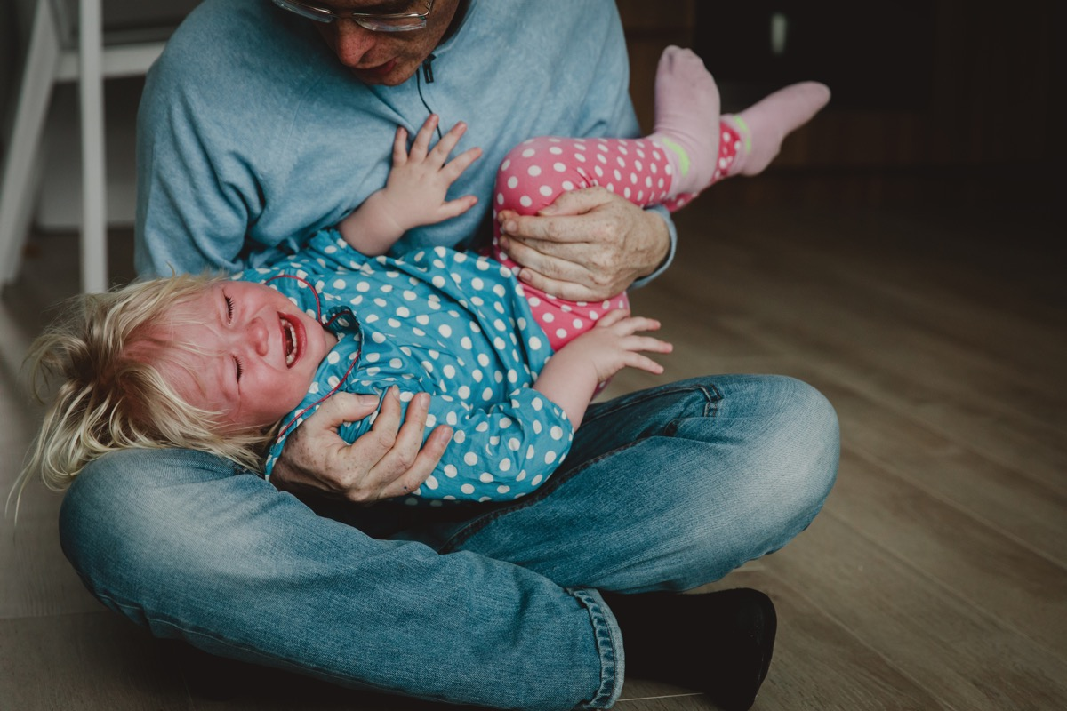 difficult parenting - dad trying to comfort shouting crying child, tired and exhausted father