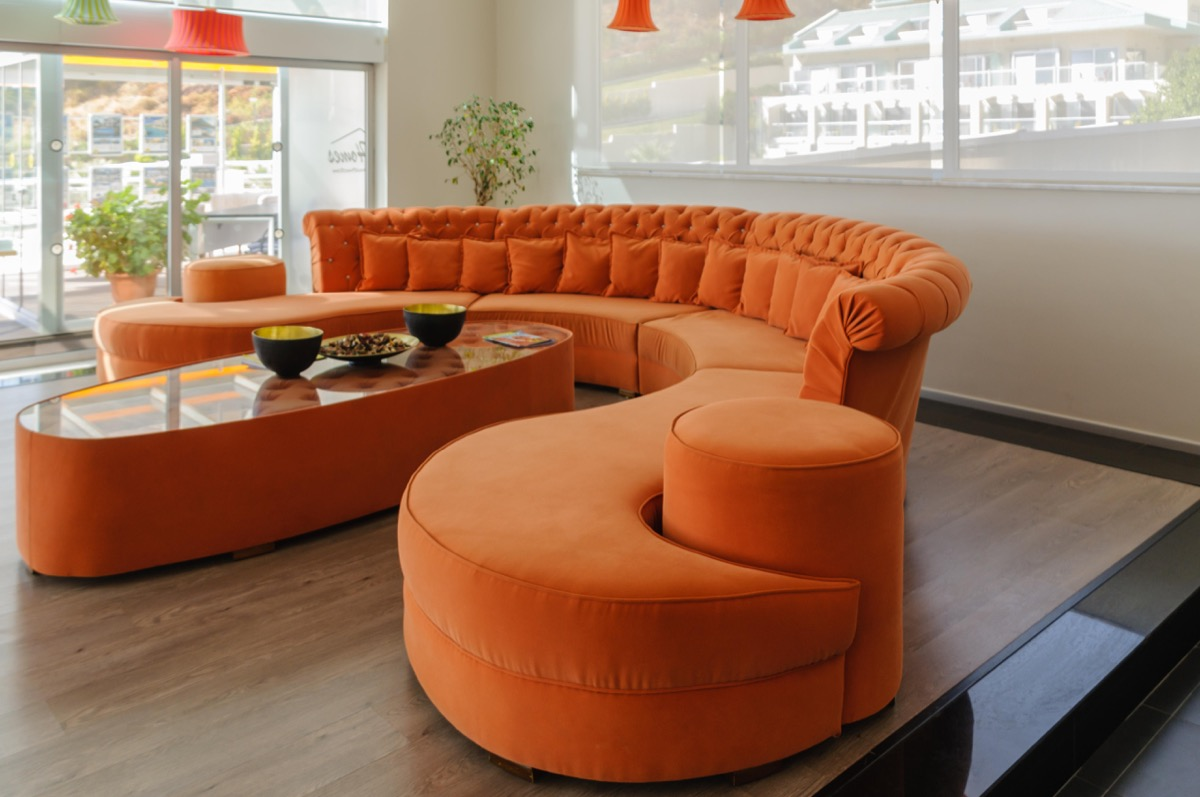 PRCJ5W Orange curved sofa and table in a large, modern, contemporary room.