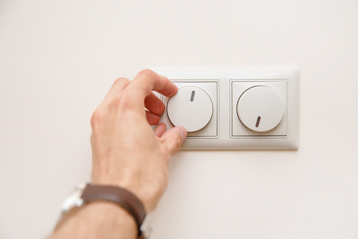 white hand turning down dimmer switch