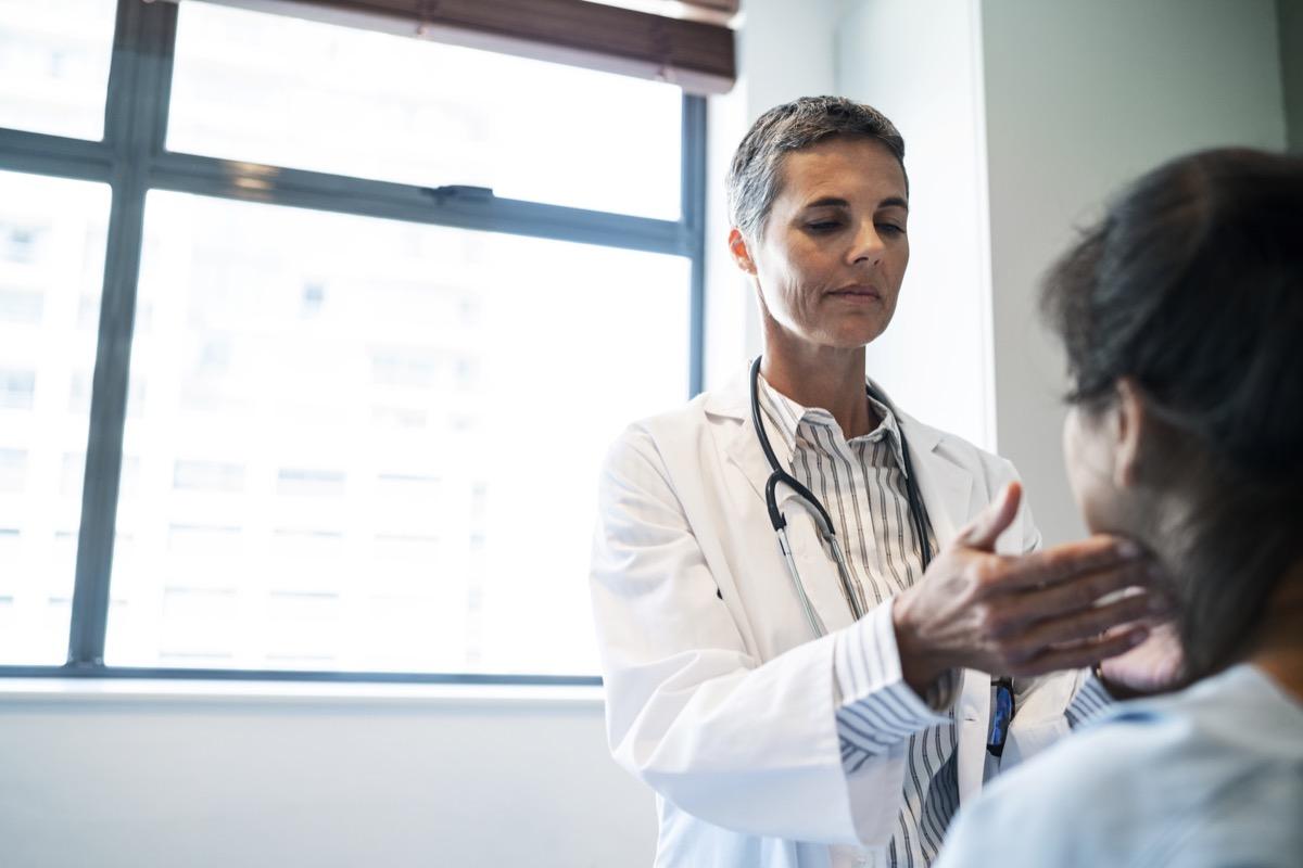 doctor examining her patient's throat