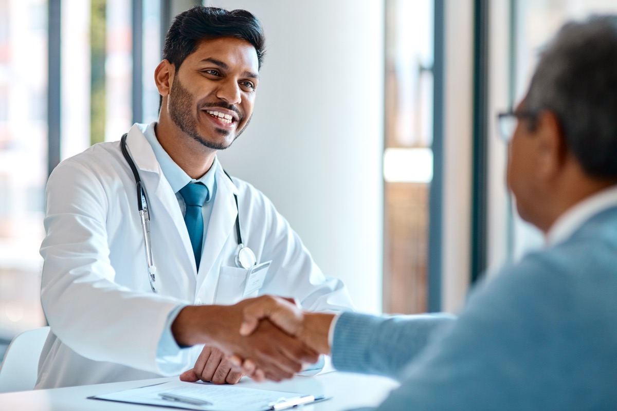 young doctor shaking the hand of his patient
