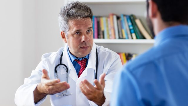 mature doctor talking to his patient looking confused