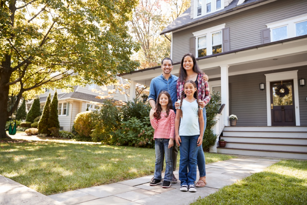 family standing in front of large suburban home, worst things about the suburbs