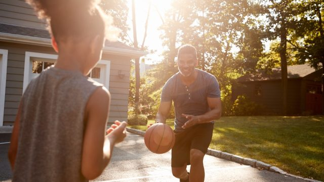 father and child playing basketball in suburbia