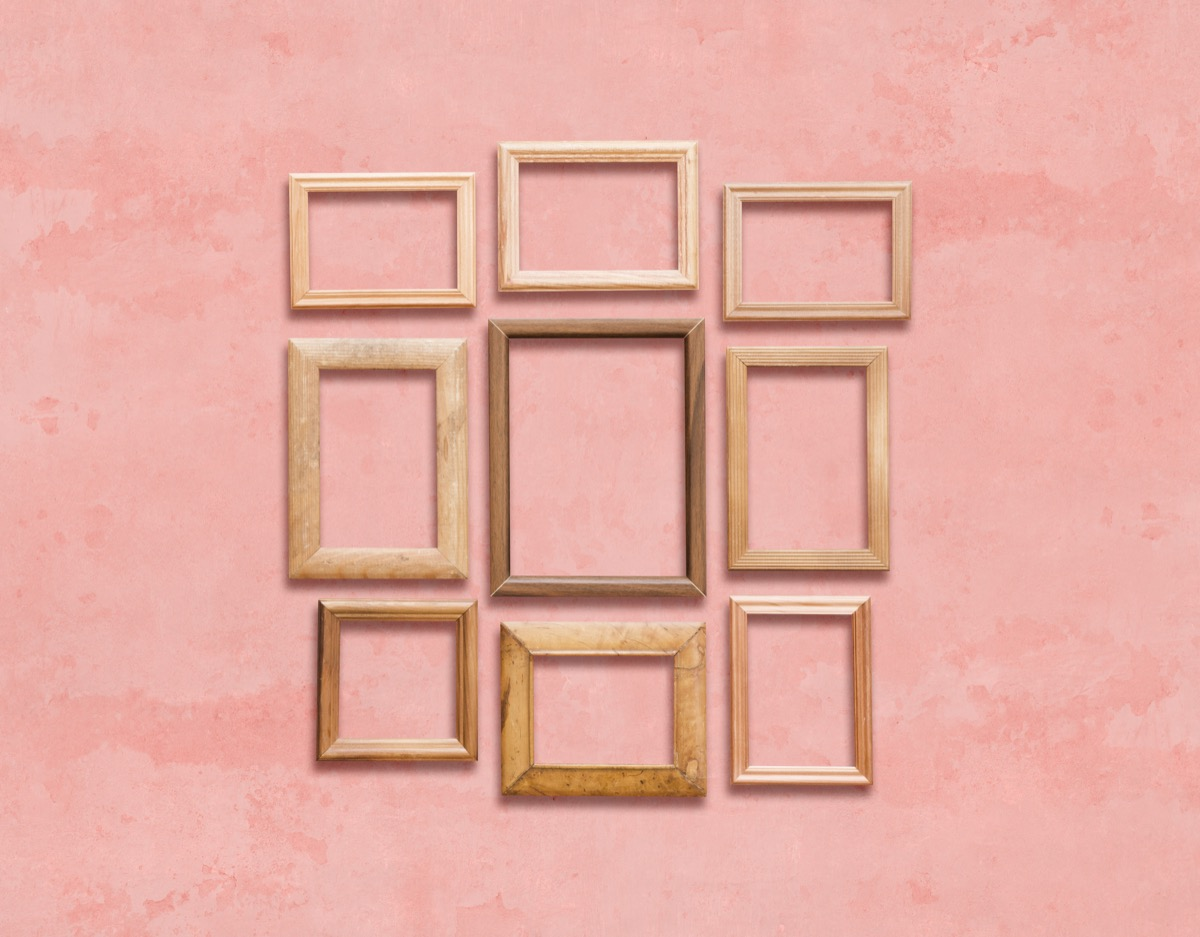 Mismatched photo frames on a pink wall vintage home trends