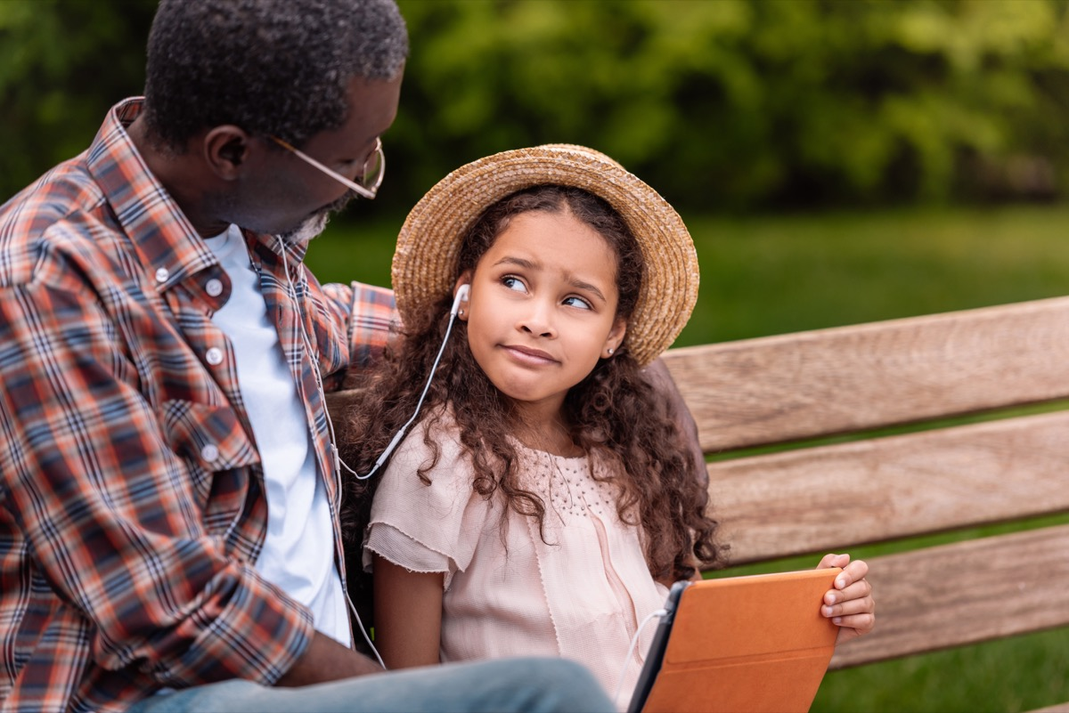 grandchild listening to music with grandfather