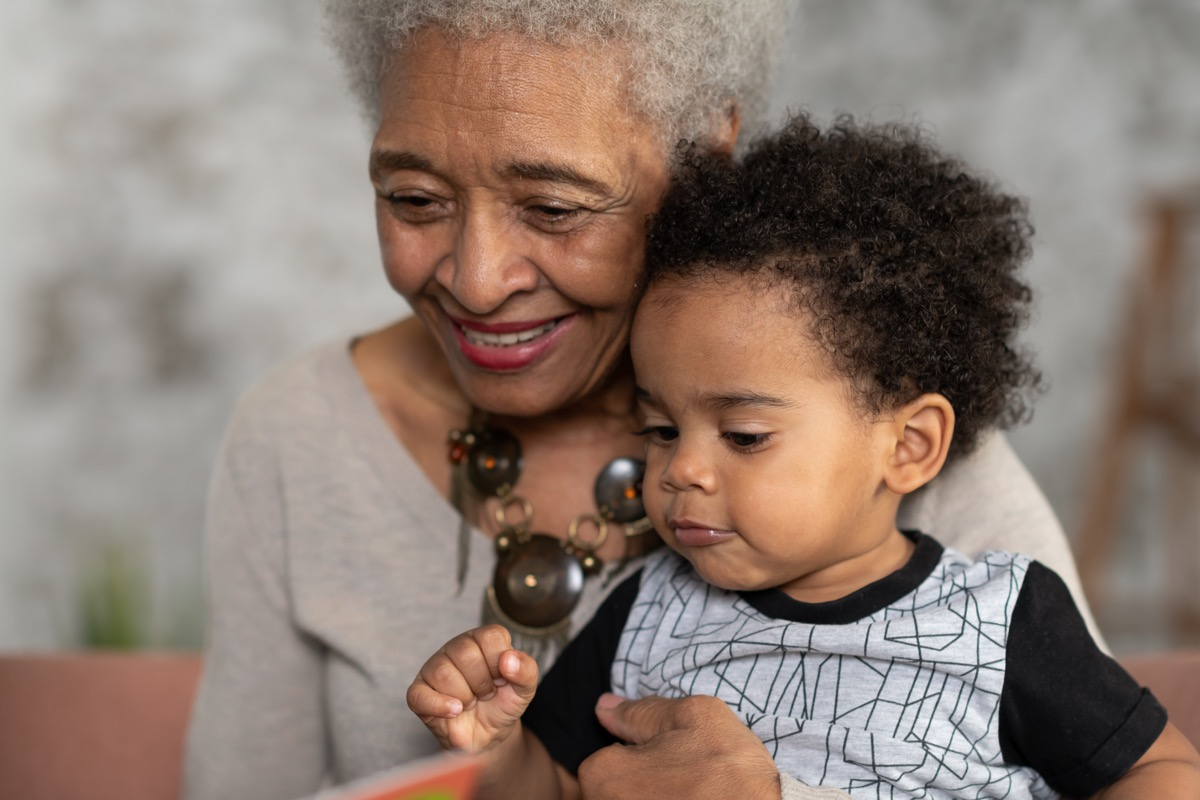 A grandmother is reading with her grandson. They are having a restful afternoon as they bond.