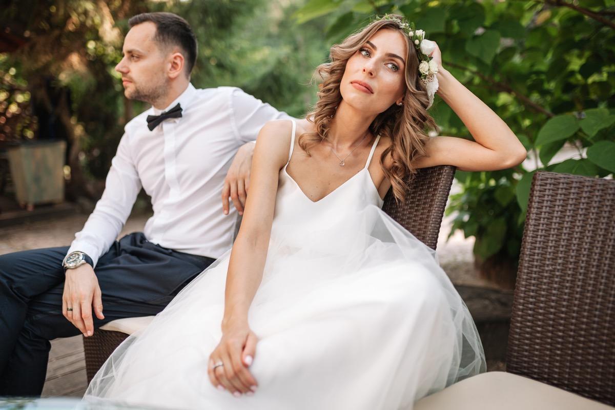 white woman in wedding dress looking sad near white husband outdoors