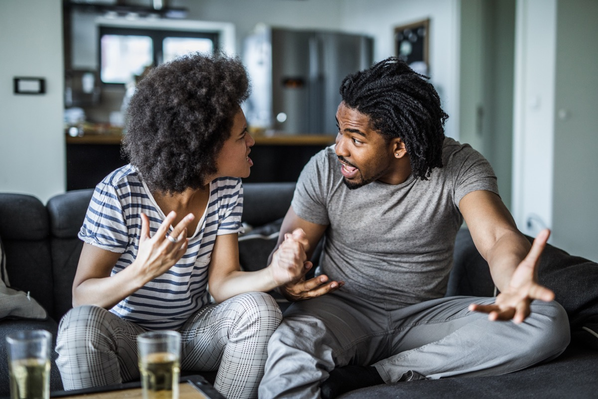 young black woman and young black man arguing with each other on the couch