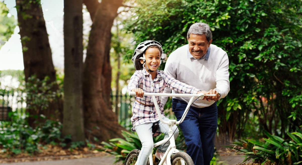 grandparent teaching his granddaughter how to ride a bike outside