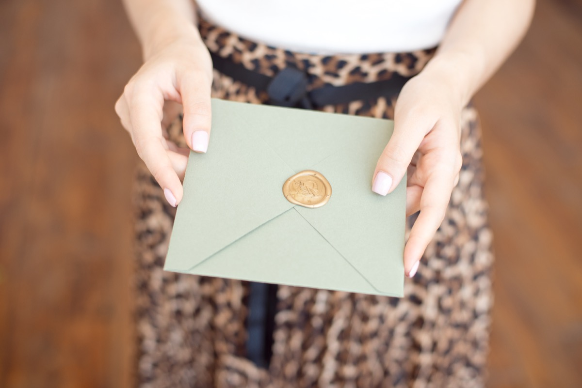 woman handing someone an invitation, old-fashioned etiquette rules