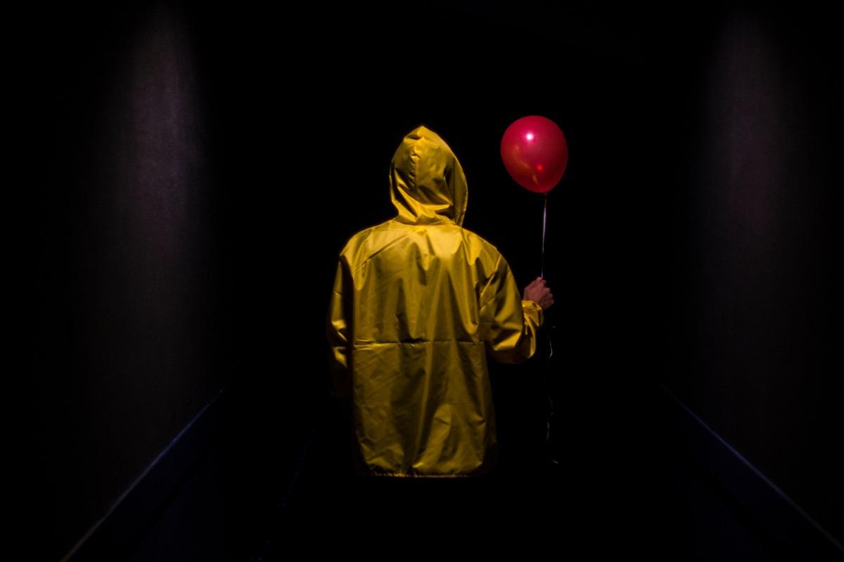 kid in yellow raincoat holding a balloon in dark hallway