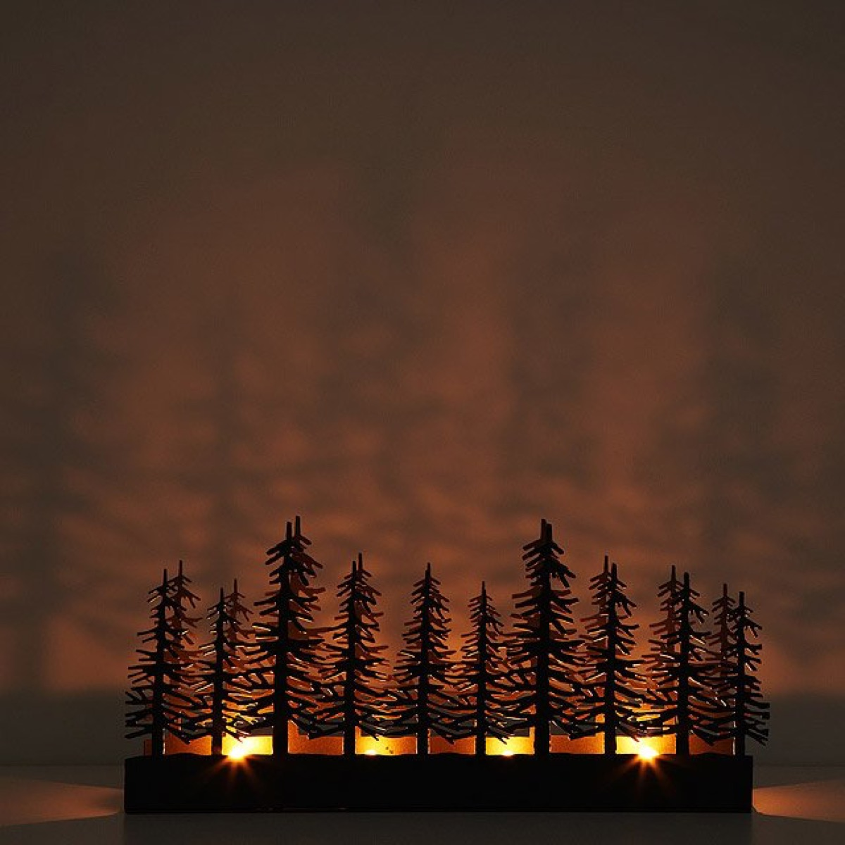 candle holder with cut out tree shapes casting shadows, fall home decor
