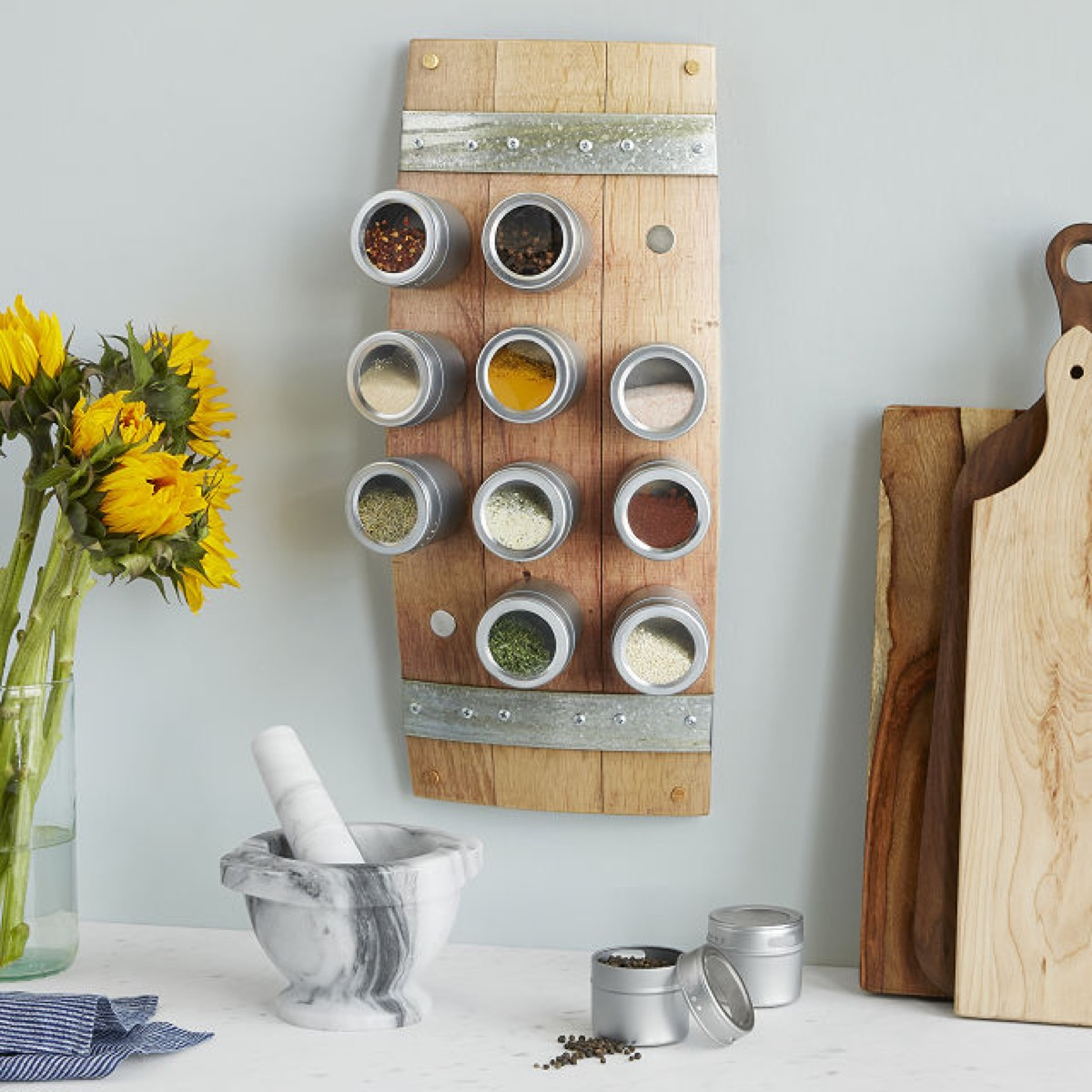 magnetic wooden spice rack next to yellow flowers, kitchen decorations