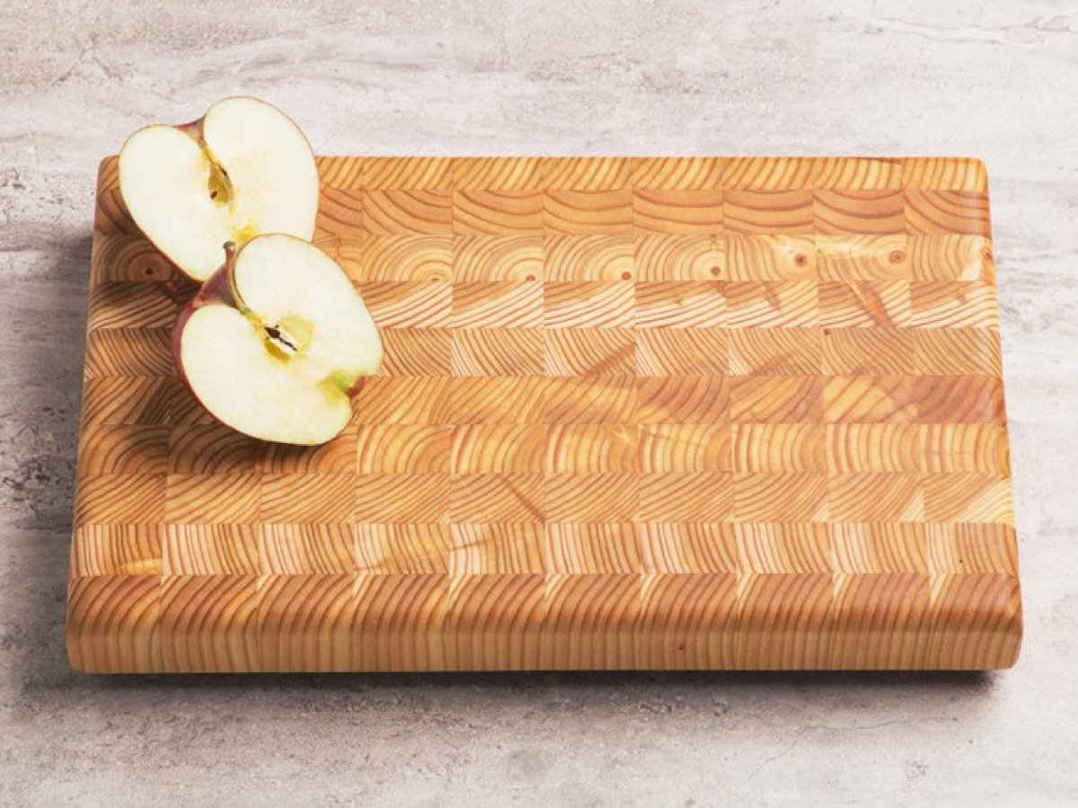 bisected apple on wood cutting board, kitchen decorations
