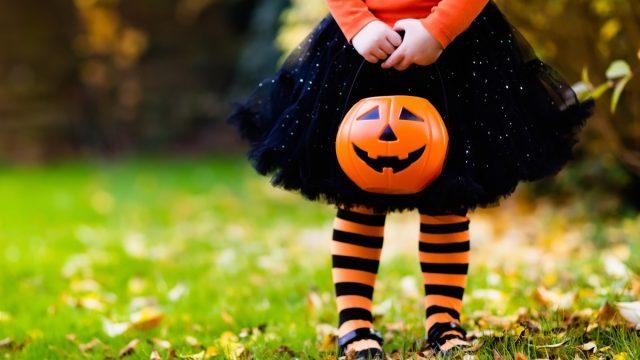 little girl holding trick or treating pumpkin on halloween