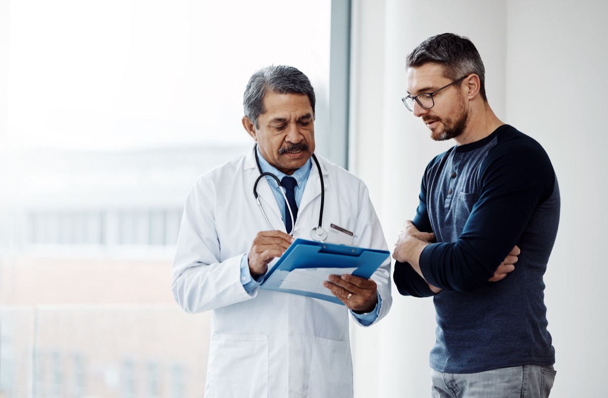 man asking his doctor questions when looking at medical papers