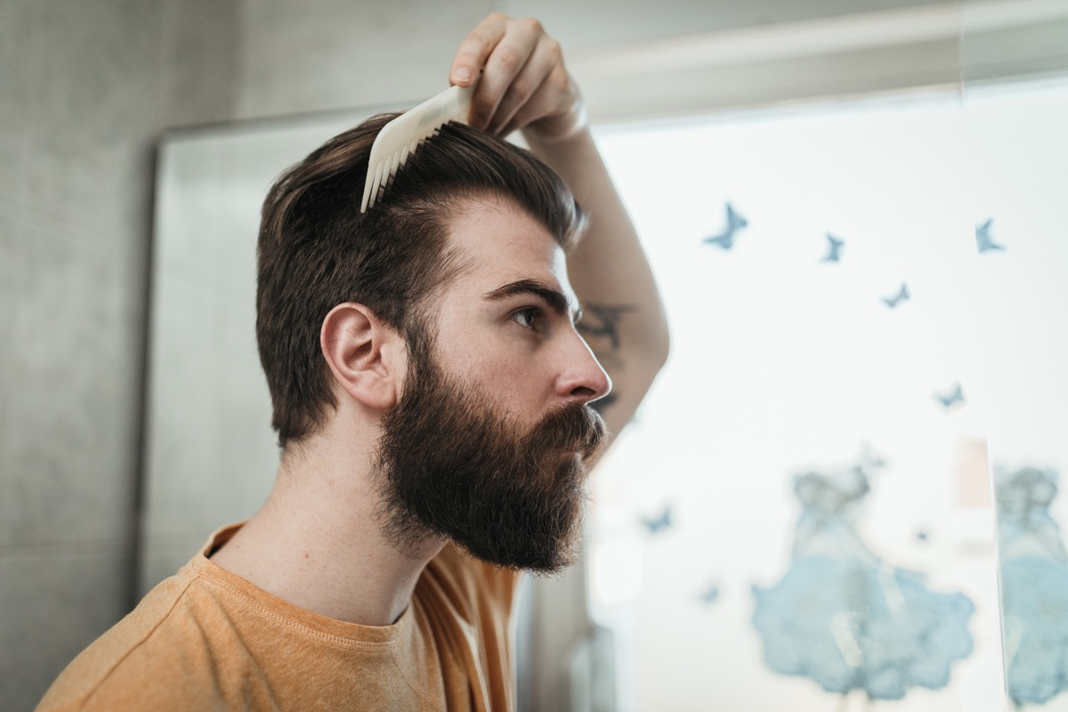 man combing hair while looking in the mirror