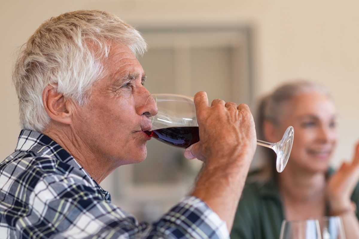 Happy senior man drinking a glass of red wine during lunch. Old man enjoying wine with friends in background. Closeup face of active and healthy senior man tasting wine.