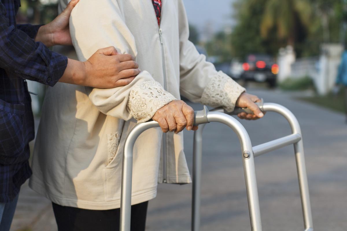man helping older woman cross the street