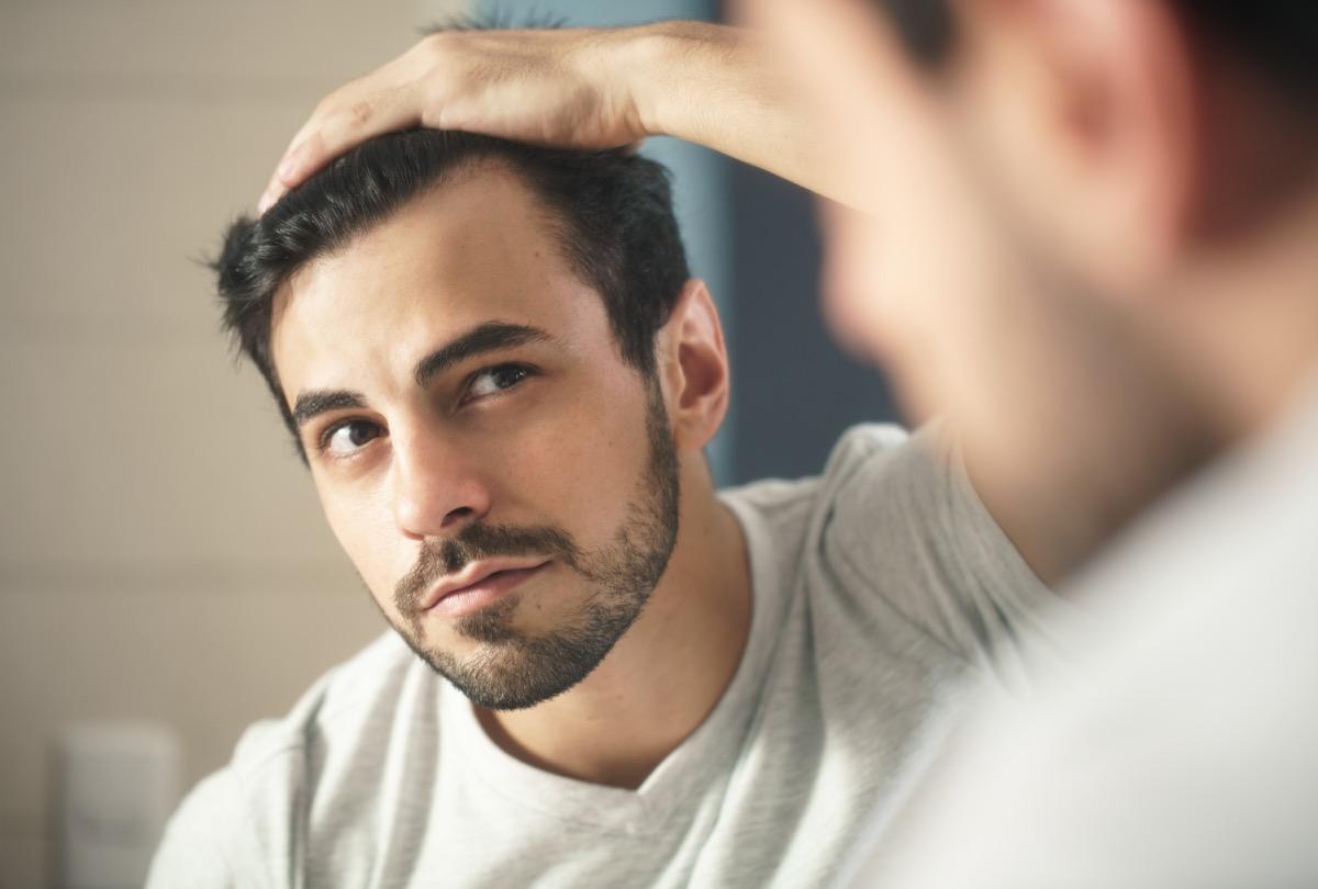 man looking in mirrors at gray hairs