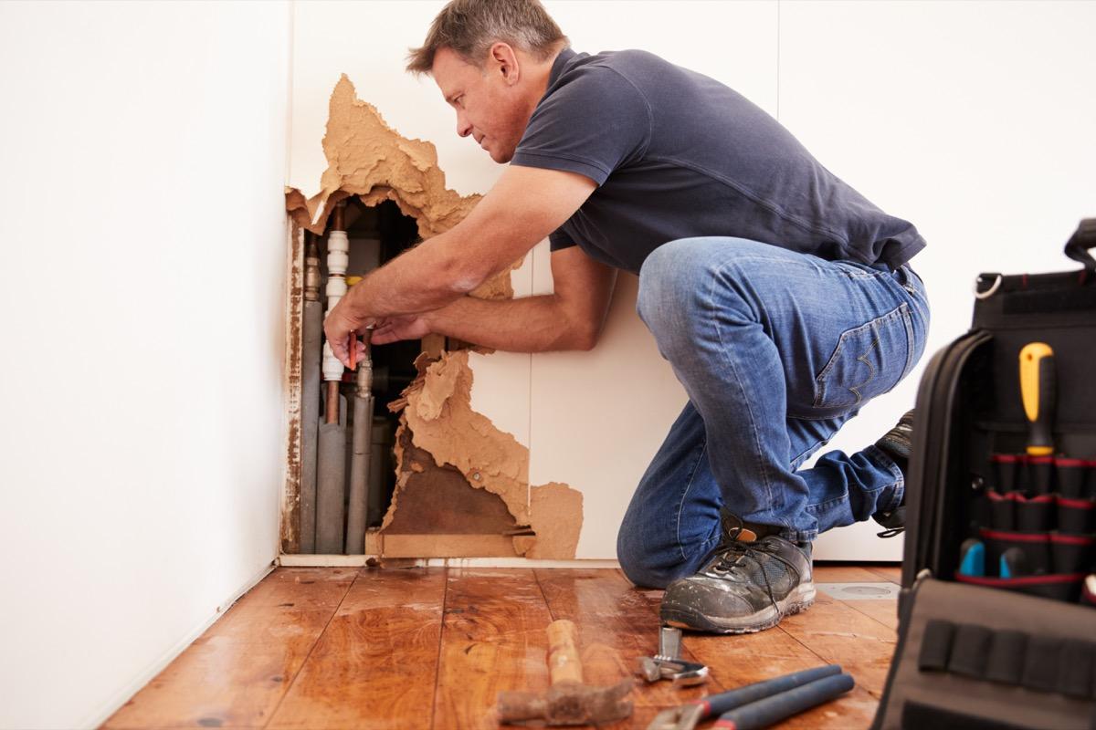 older man repairing damaged wall
