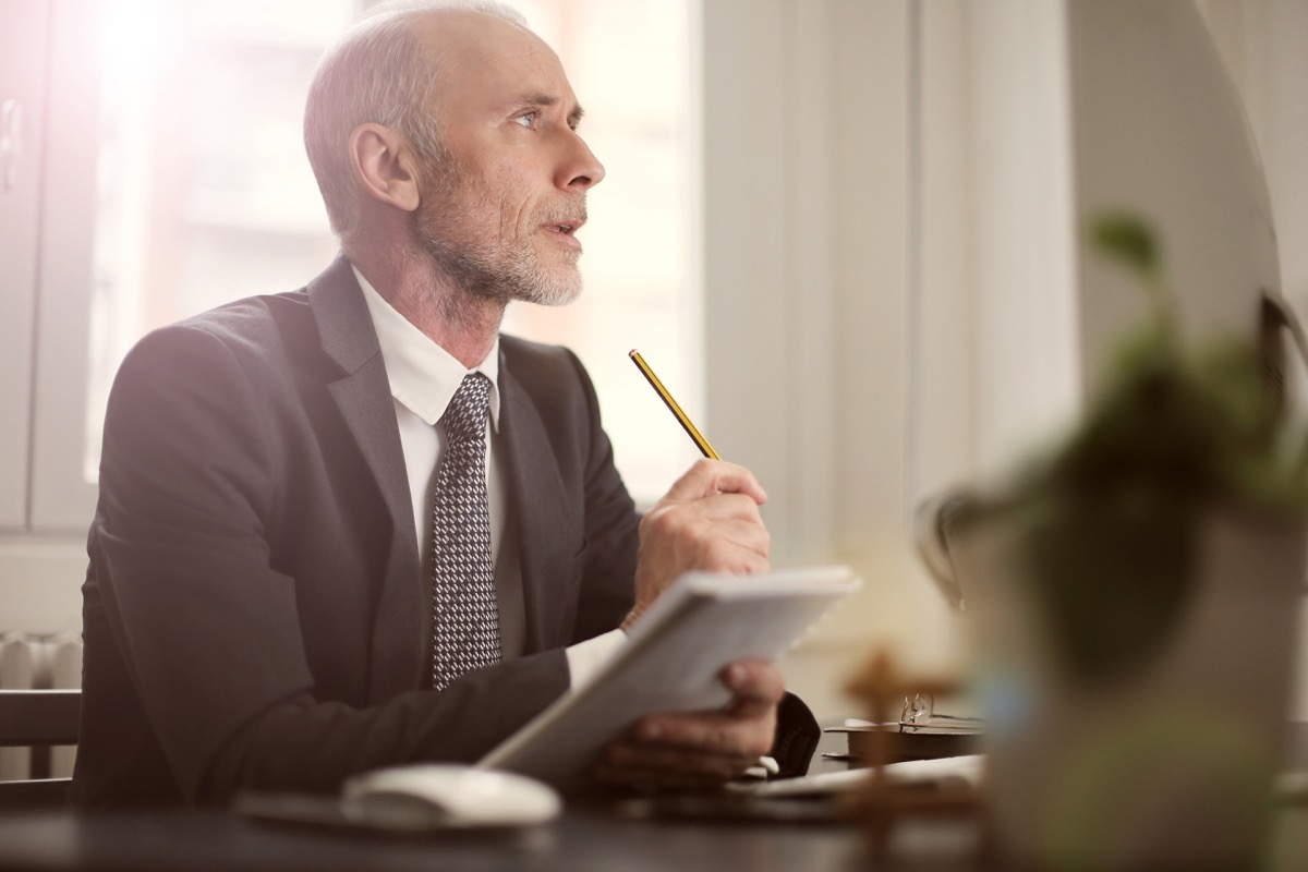 a man sitting at a desk and writing while thinking