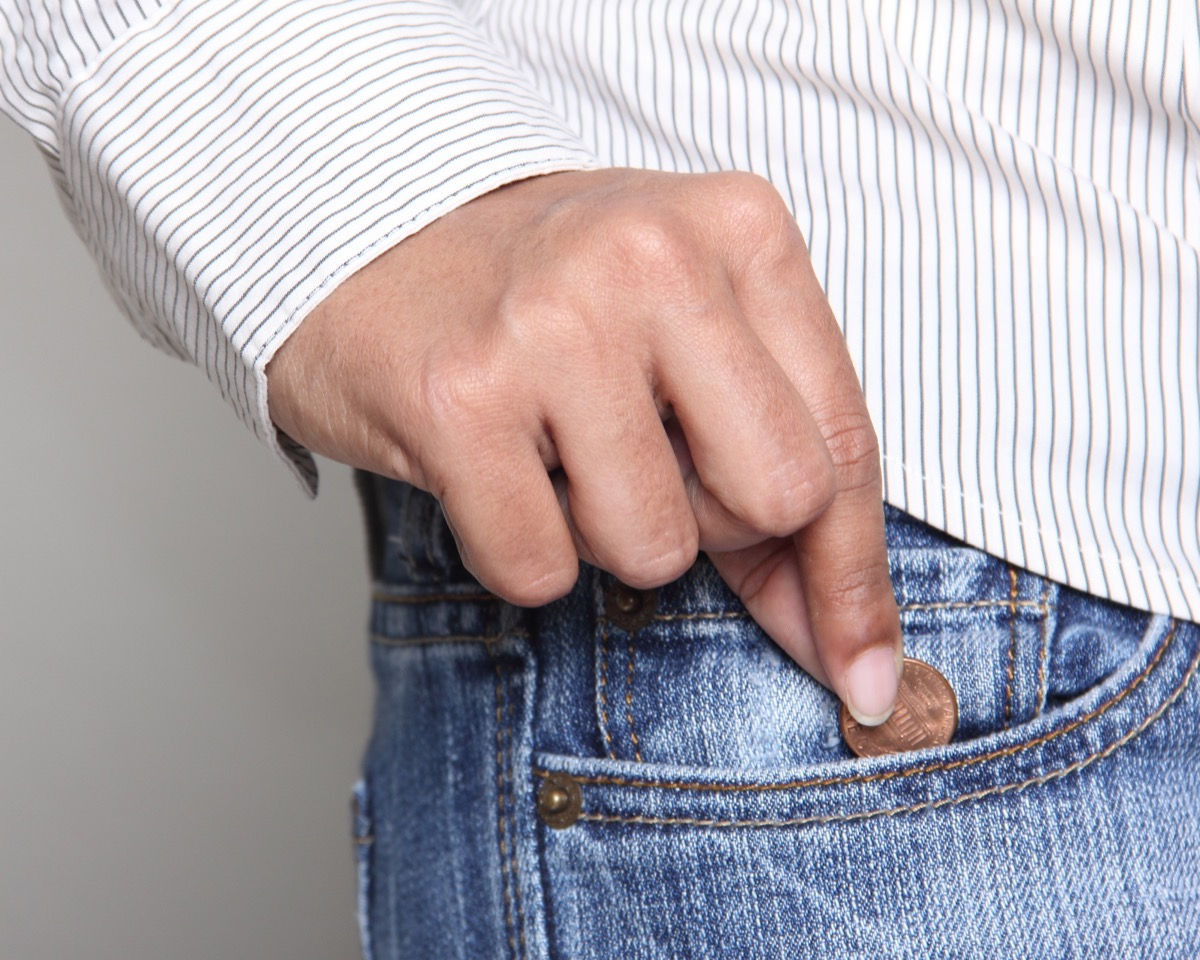 man putting lucky penny into his pocket