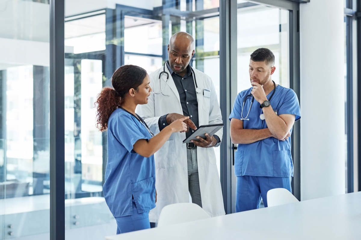 group of medical practitioners talking to each other while looking at a tablet