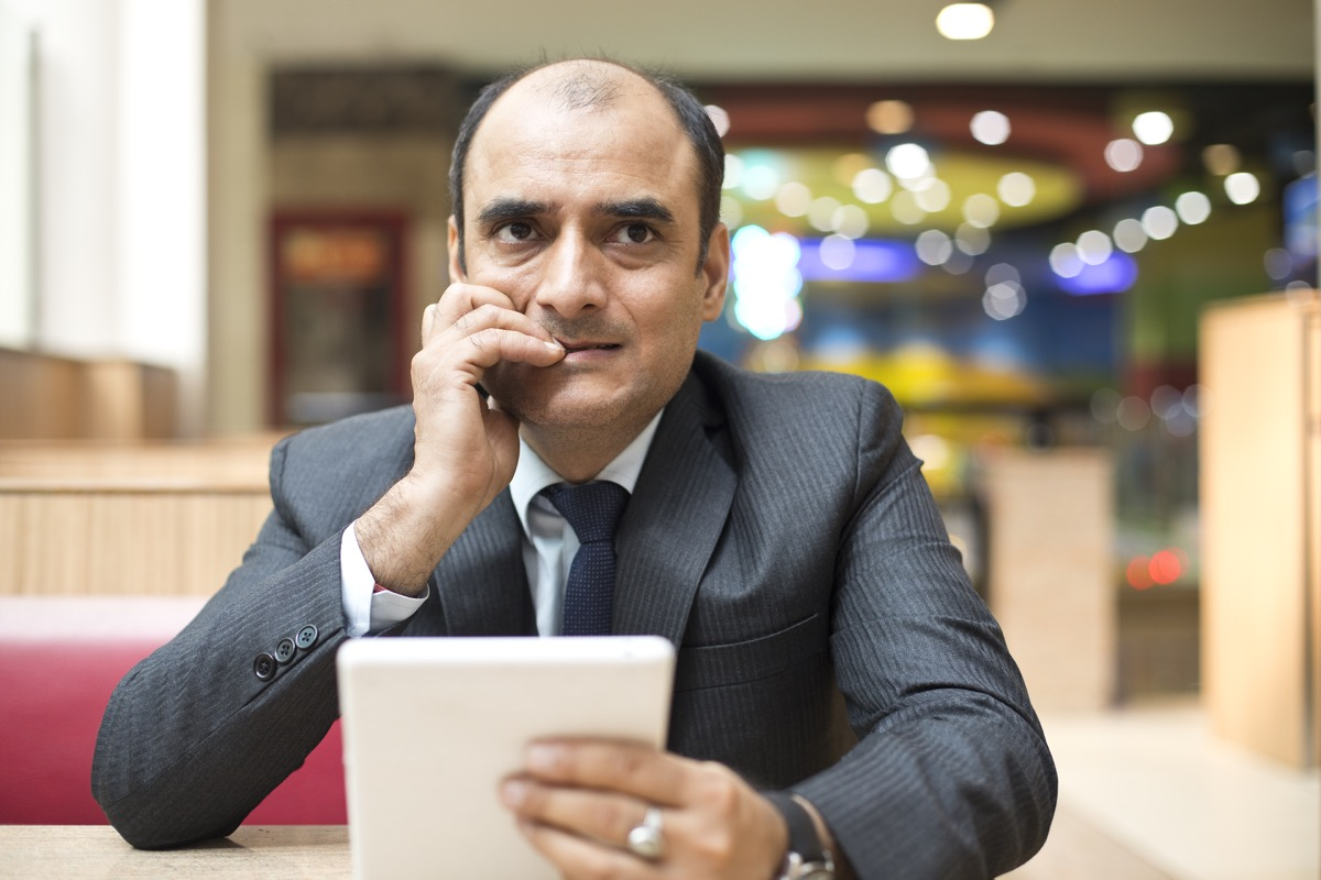 Serious businessman using digital tablet at cafe