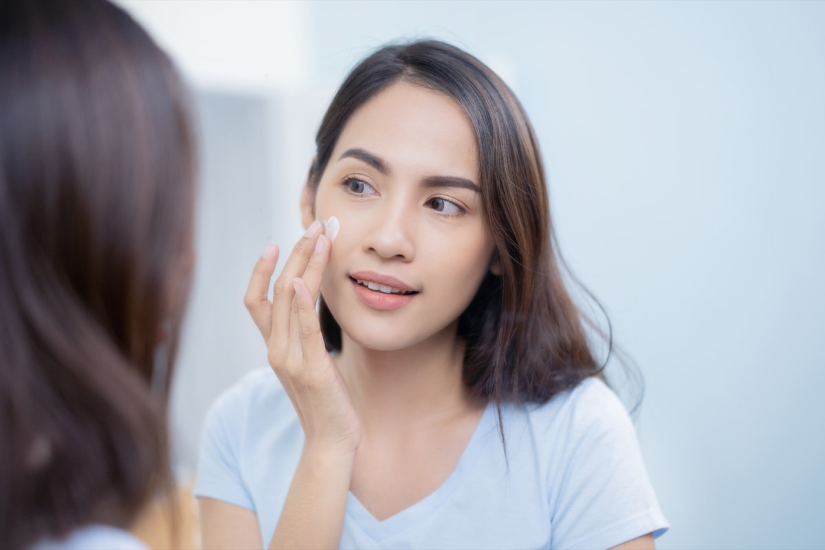 woman applying moisturizer, using objects wrong