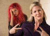 Cool mother making hand gesture with embarrassed teenager