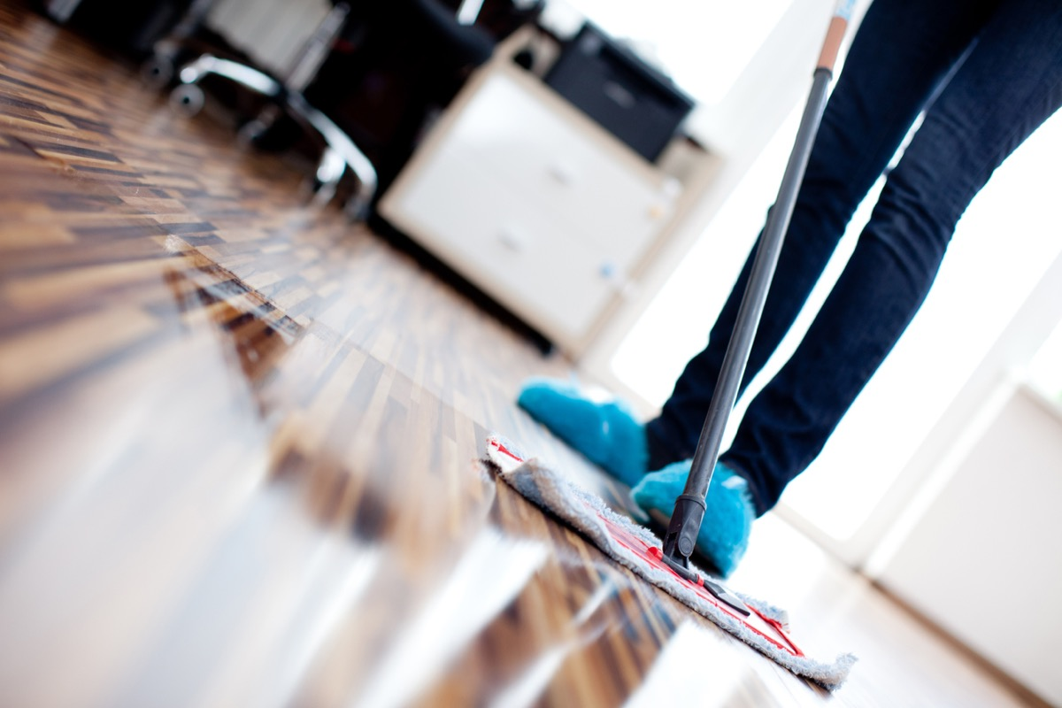 person using mop to clean hardwood floor