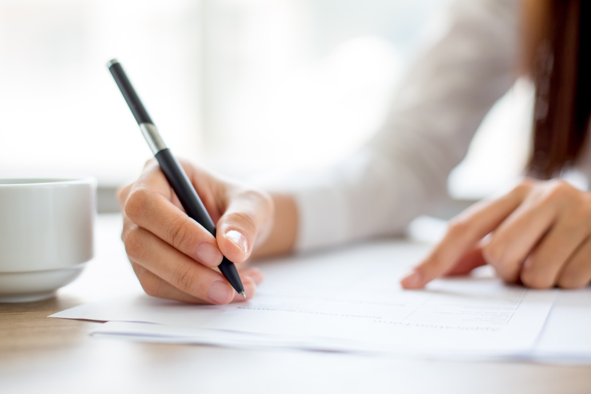 Woman using a pen to write at her desk office germs