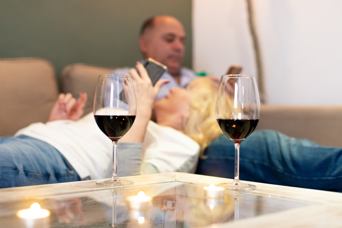 Two glasses of red wine on table with senior couple relaxing in background on sofa with smartphones in their hands. (Two glasses of red wine on table with senior couple relaxing in background on sofa with smartphones in their hands., ASCII, 116 compon