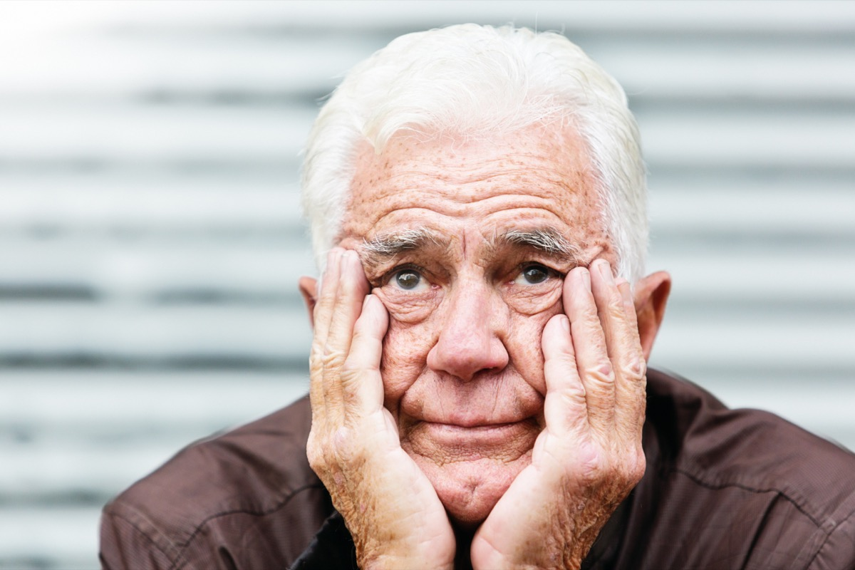 An unhappy old man, his head in his hands looks at camera, frowning.