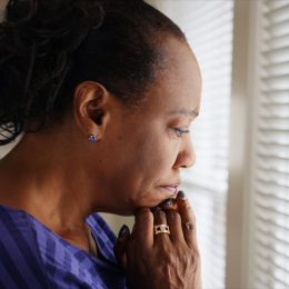 older woman looking out window looking sad