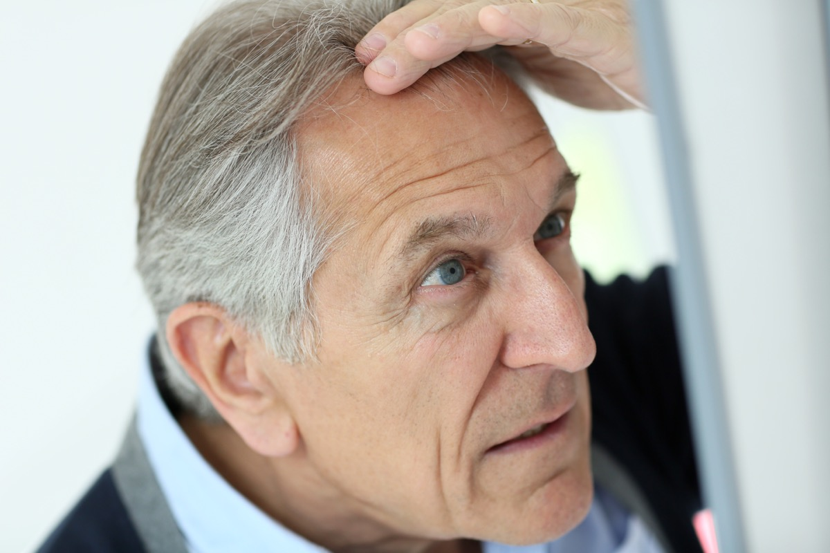 man looking at his gray hair in the mirror